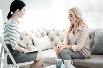 Emotional state. Upset depressed woman sitting on sofa while female psychologist listening to her