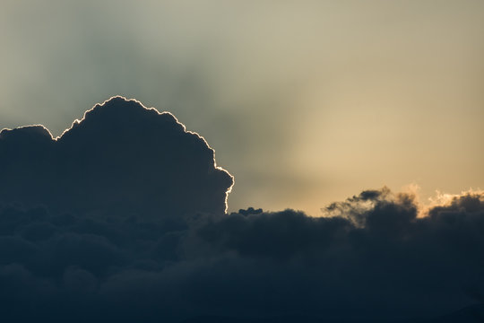 Sun hidden behind dark clouds on sunset. Ray of light. Copy space. Background.