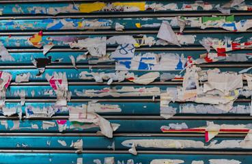 Blaues Rolltor mit Plakatresten