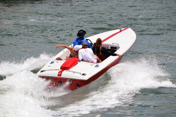 Sport high end runabout motorboat with four passengers aboard speeding across the Florida Intra-coastal Waterway off Miami Beach.