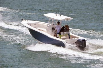 Helmsman and two passengers enjoying a sightseeing cruise on the florida intra-Coastal Waterway off Miami Beach