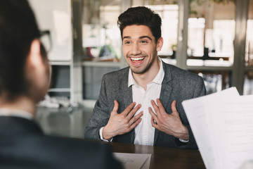 Business, career and placement concept - surprised caucasian man 30s rejoicing and showing at himself when hiring, during job interview with employees in office