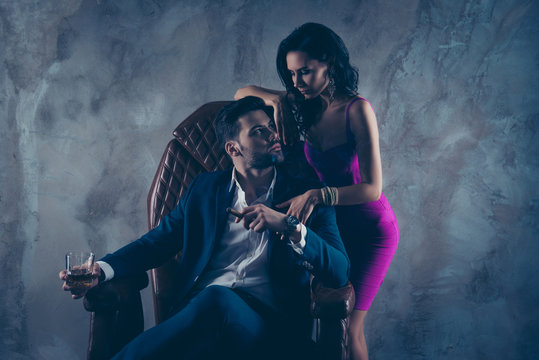 Portrait of harsh boss in formalwear sitting in leather chair holding glass with cognac cigar in hands, seductive tempting lady standing near looking at each other isolated on grey background