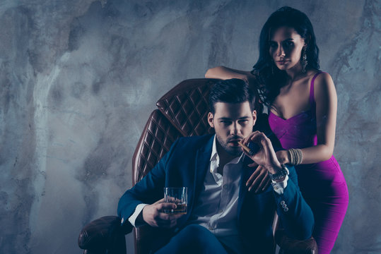 Portrait of brutal gentleman in formal wear sitting in leather chair holding glass with whiskey cigar in hands, charming pretty lady standing near looking at camera isolated on grey background