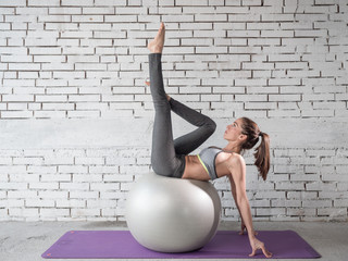 Beautiful fitness girl with silver ball doing exercises. Healthy lifestyle and sports concept. Series of exercise poses.