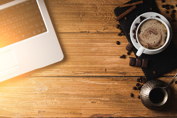 workplace of young freelancer man or woman with coffee, laptop, smartphone in morning on wooden table