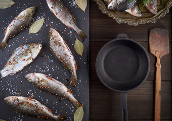 river fish on a black board and a black cast-iron frying pan