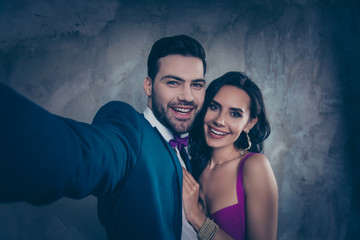 Self portrait of attractive trendy couple, gentlemen with stubble in tuxedo shooting selfie on front camera with pretty charming lady embracing, isolated on grey background wedding concept
