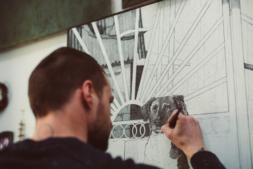 Man is drawing a dog with a black pen view behind, blurred foreground