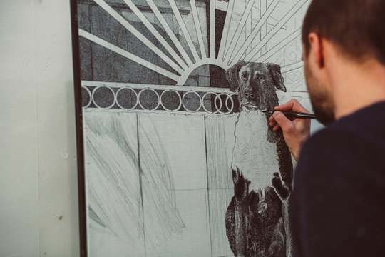 Portrait of male artist drawing a dog with a black pen on big canvas behind