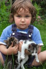 Kleinkind im Garten hält vier Wochen alte Katzenwelpen