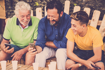 complete family caucasian people men sitting on a wood bench looking smartphones. grandfather father and son all together enjoying the leisure outdoor time with smile and fun. technology