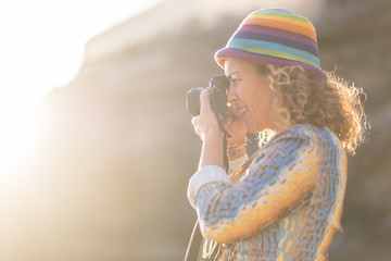 woman caucasian photographer with nice coloured hat taking pictures with old little camera. sunlight and sun flare in the background. bright summer concept image of nice people active taking memories