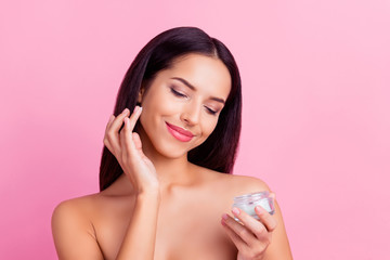 Charming, pretty, attractive, nice, cute woman  applying face cream for problem, combined skin, holding bank with lotion, isolated on pink background