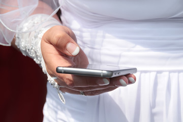 Frisch verheiratete Braut hält Mobiltelefon und versendet neueste Nachrichten