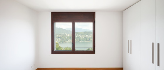 White empty room with windows overlooking the lake and large white wardrobe