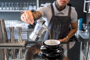 Cafe with young barista in apron pouring black coffee from coffee pot in contemporary design interior. Breakfast time