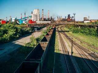 Cargo freight train wagons go on railroad in industrial zone with plants and manufacturing factories of heavy industry