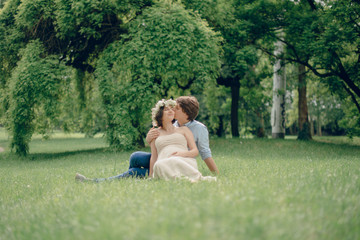 Happy pregnant woman and her husband sitting on the blanket in the green meadow in the park. Sunny summer day