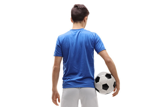 Rear view shot of a teenage soccer player holding a football