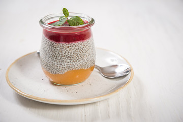Glass jar with greek yogurt and strawberry and orange mousse