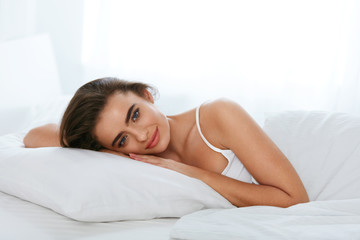 Woman With Pillow Resting On Bed