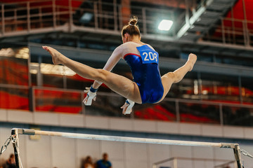 women gymnast exercises on uneven bars in artistic gymnastics