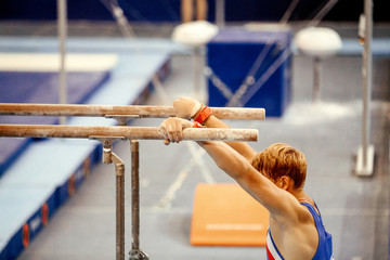 men gymnast exercises on parallel bars in gymnastics