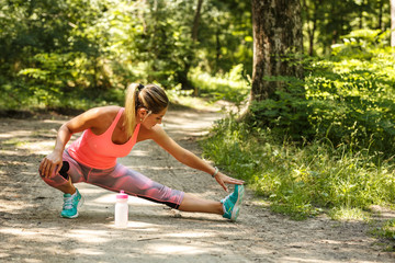 Young woman stretching and relaxing after jogging outdoor.Green environment.
