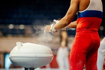 gymnast rubs chalk on his hands at gymnastics exercises on horizontal bar