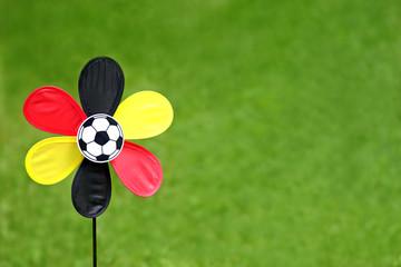 scharz-rot-goldenes Windrad mit Fußball auf grünem Rasen