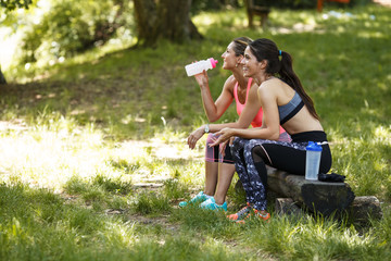 Two young woman sitting at the park and relaxing after jogging outdoor.Green environment.