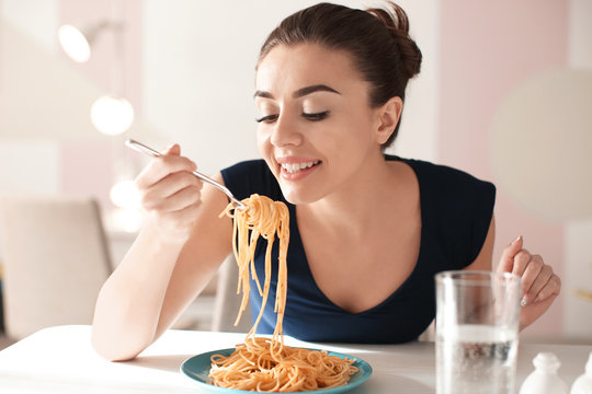 Young woman eating tasty pasta in cafe