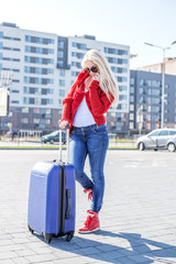 Young woman speaks by mobile phone. Suitcase. The concept of travel, work, lifestyle.