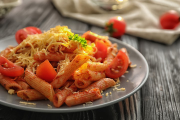 Plate of tasty penne pasta with tomato sauce on wooden table, closeup
