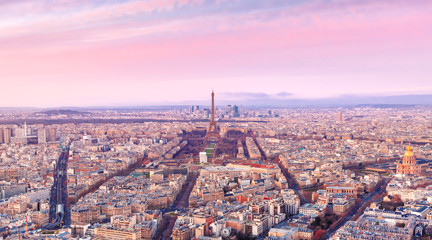 Aerial panormic view of Paris skyline with Eiffel Tower, Les Invalides and business district of Defense at pink sunset, as seen from Montparnasse Tower, Paris, France