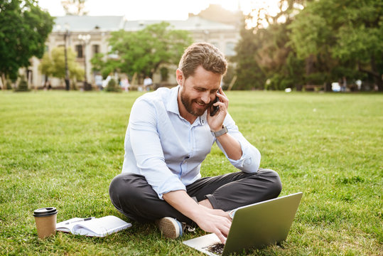 Photo of adult european man in business clothing, sitting on grass in park with legs crossed and speaking on mobile phone while working on silver laptop
