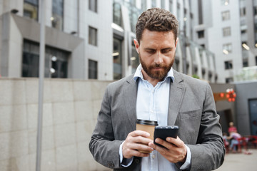 Photo of adult man in gray suit looking at mobile phone in hand, while standing with takeaway coffee in front of modern business center
