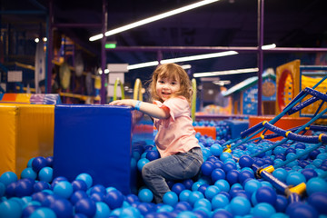 Happy little girl child in colourful blue plastic balls pool.