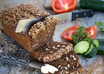 angeschnittener Brotlaib mit Butter, Gurke und Tomate zum belegen