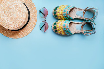 Summer fashion flatlay with gradient round sunglasses, straw hat and espadrille sandals on the blue background. Perfect beach set for holidays on the sea. Marina style.