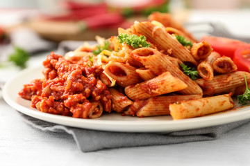 Plate with tasty penne pasta and bolognese sauce on table, closeup