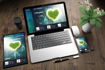 Wall Mural - tablet, laptop and mobile phone over wooden desktop showing honeymoon website