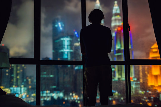 Man looks out the window at the night city