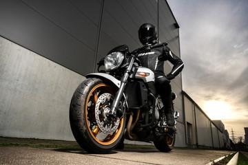 Motorradfahrer posiert im Industriegebiet