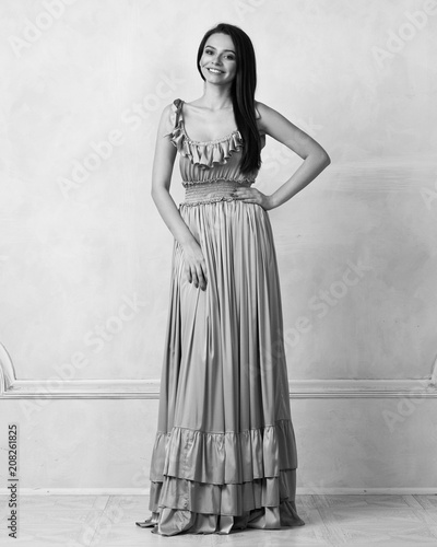 f1ac6b95ceb75 ... brunette woman dressed in exquisite nude ball gown with lace top.  Attractive female model in elegant dress posing against white wall on  background.