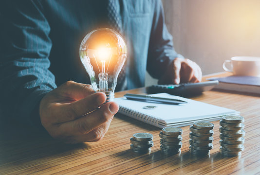 business man holding light bulb on desk in office and putting calculator with coins or money on work desk also for idea,energy,finance concept.