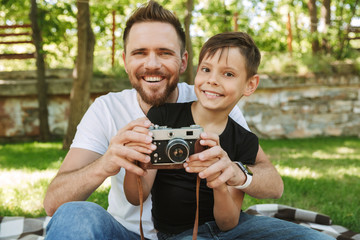 Young father sitting with his little son holding camera photographing.