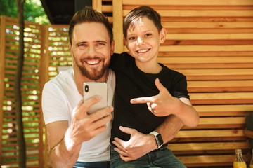 Happy young father sitting with his little son using mobile phone pointing.