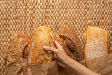 A female hand picking a loaf of bread from various kind of bread on weave grass background.